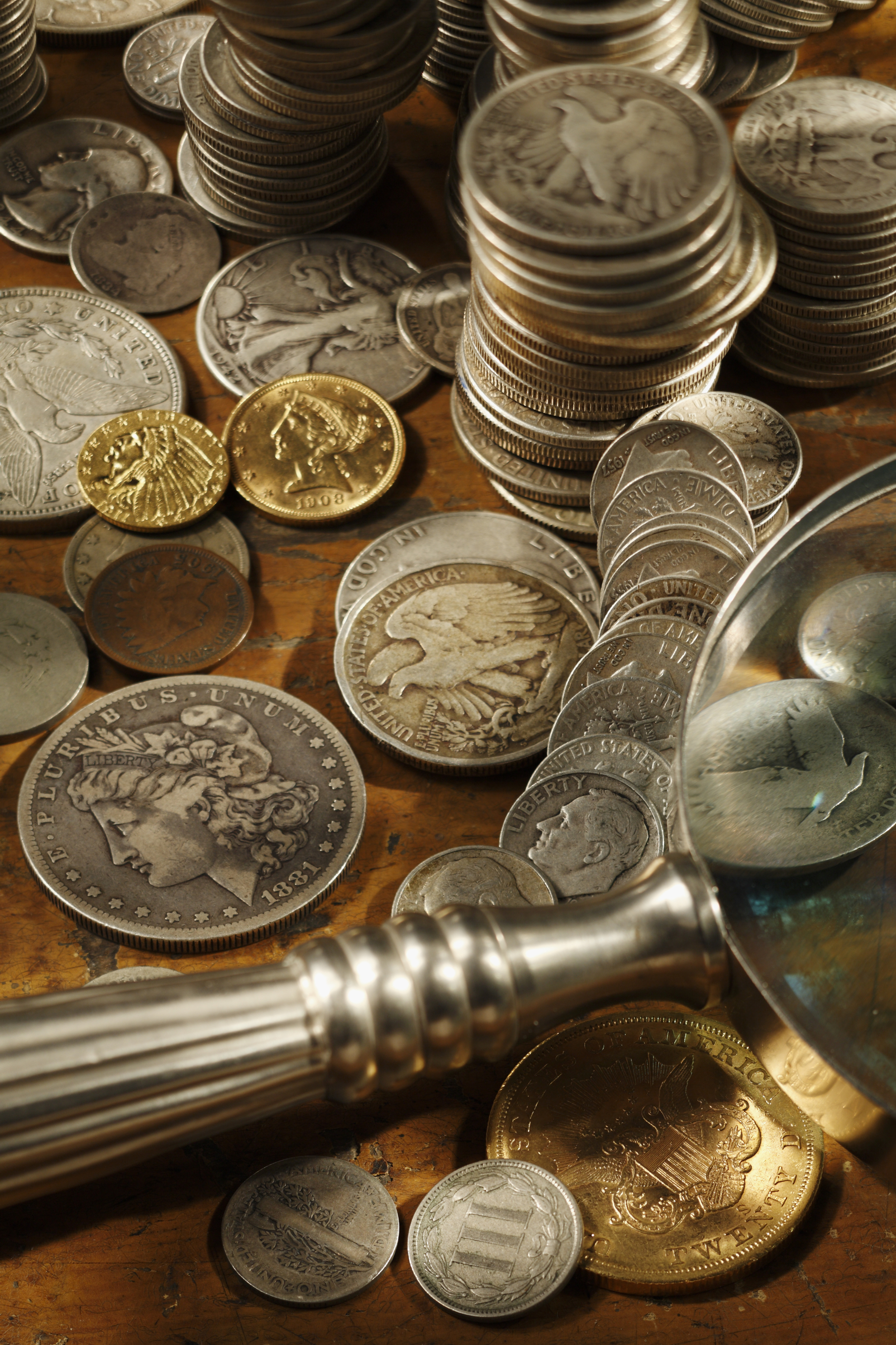 Silver and gold coin collection on a wooden table.  Magnifying glass is quite at home as those collecting usually need a little help spotting the dates and mint marks.  Grading coins is a bit of a science but those who have coins that are not worth the value of having them graded are forced to make those assumptions themselves to determine what a coin is worth.  Shot on a Canon 5D.